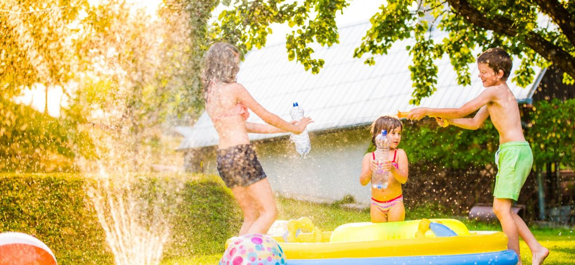 Boy splashing girls with water gun in the garden