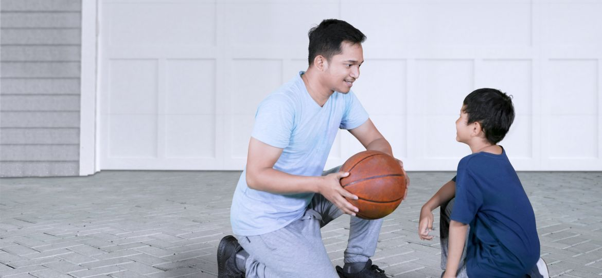 Father teaching his son to play basketball