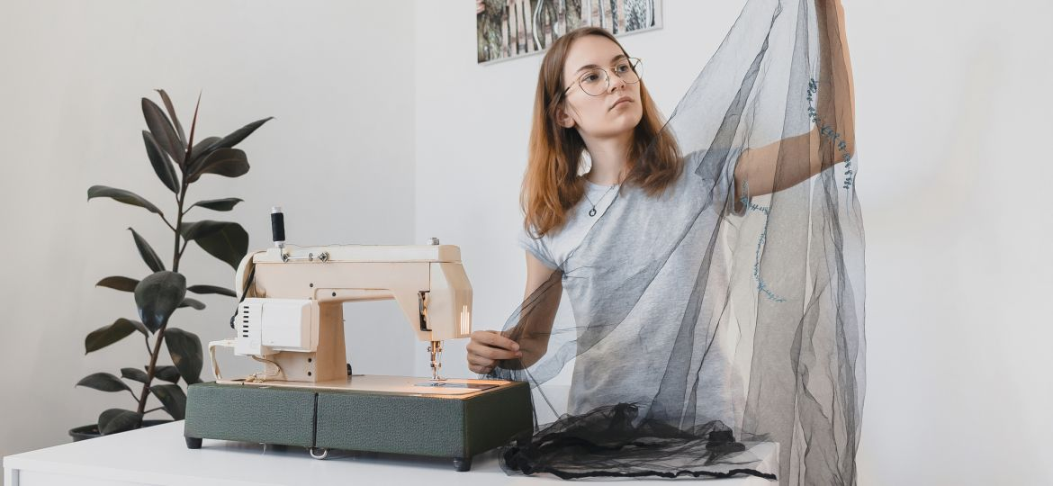 The girl Sewing dress made of black fabric tulle on a vintage sewing machine in the room workplace handmade