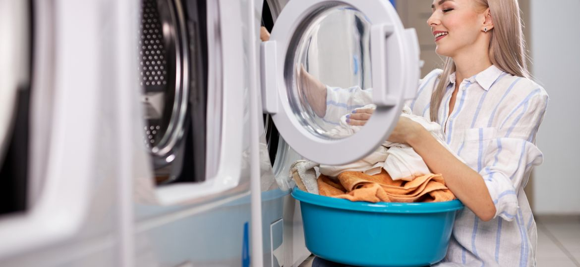 Caucasian woman doing the daily chores - laundry. Female folded clean clothes in the laundry basin