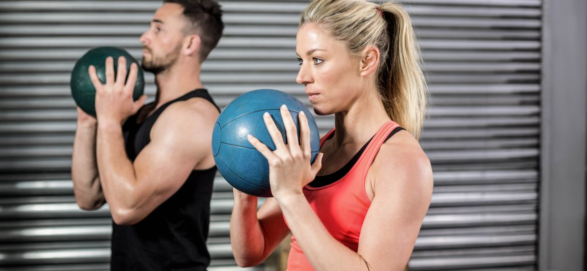 Couple doing ball exercise at crossfit gym